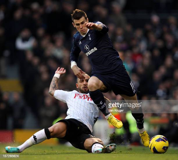 Gareth Bale of Tottenham is tackled by Ashkan Dejagah of Fulham during the Barclays Premier League match between Fulham and Tottenham Hotspur at...