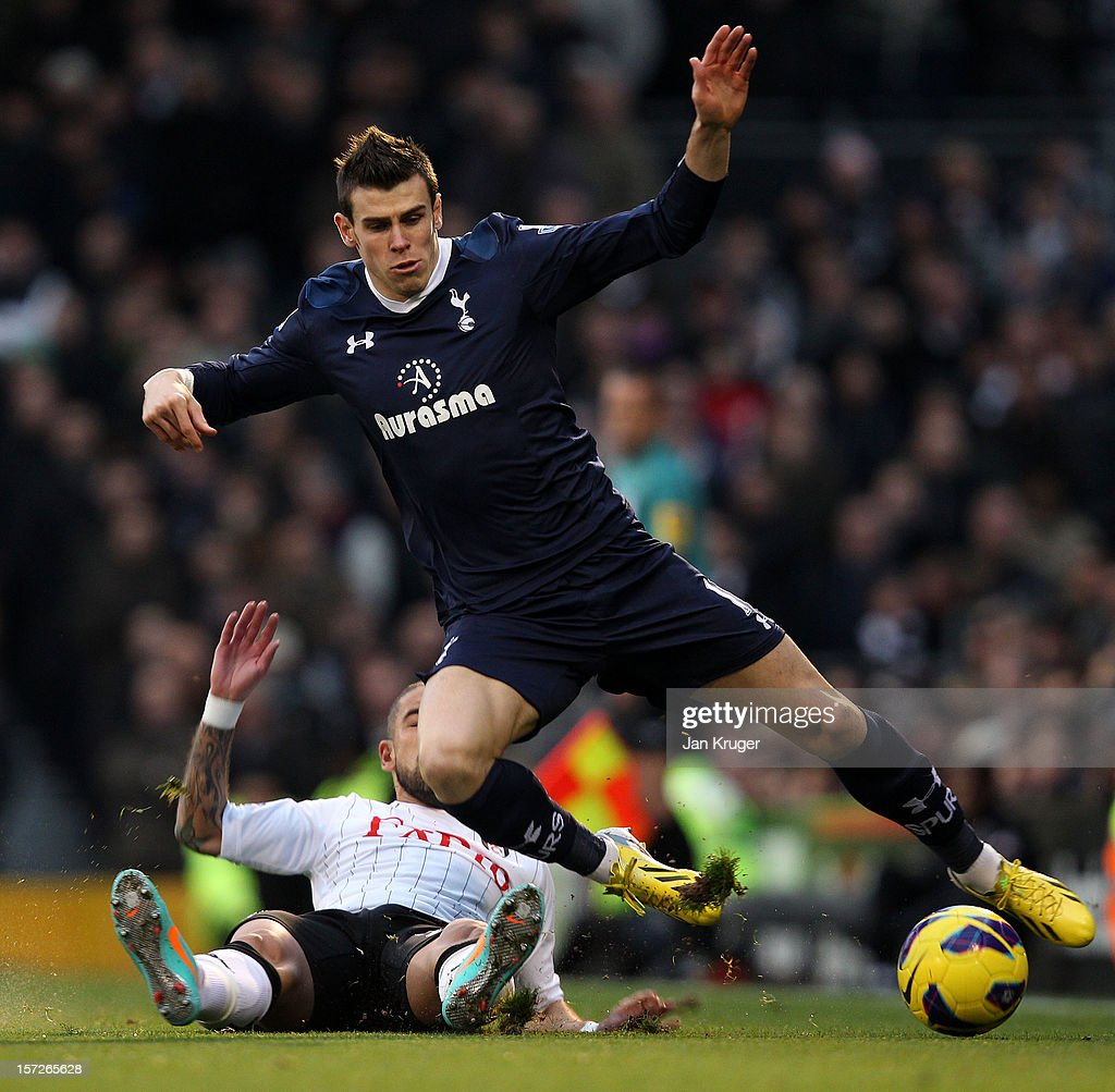 Gareth Bale of Tottenham is tackled by Ashkan Dejagah of Fulham during the Barclays Premier League match between Fulham and Tottenham Hotspur at Craven Cottage on December 1, 2012 in London, England.