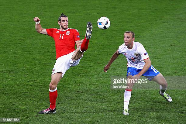 Gareth Bale of Wales and Denis Glushakov of Russia compete for the ball during the UEFA EURO 2016 Group B match between Russia and Wales at Stadium...