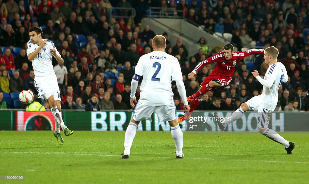 Gareth Bale (2nd R) of Wales has a shot on goal during the international friendly football match between Wales and Finland at Cardiff City Stadium in Cardiff, south Wales on November 16, 2013. The match ended 1-1.