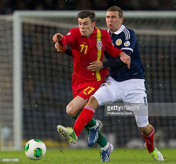 Gareth Bale of Wales is tackled by James McArthur of Scotland during the FIFA 2014 World Cup Group A Qualifying match between Scotland and Wales at...