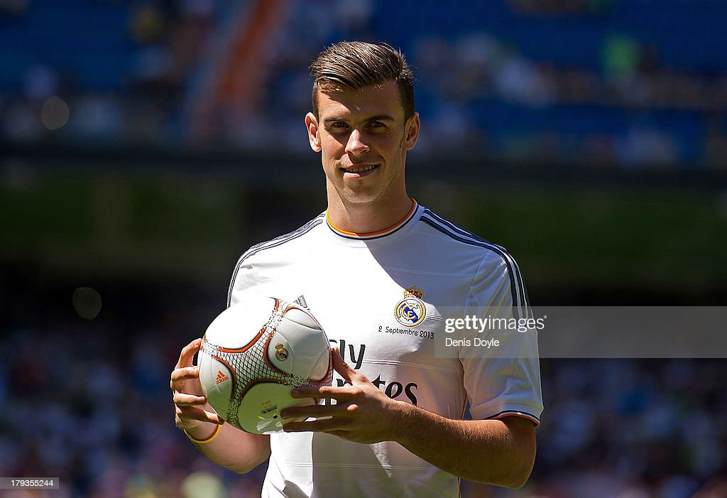 <a gi-track='captionPersonalityLinkClicked' href=/galleries/search?phrase=Gareth+Bale&family=editorial&specificpeople=609290 ng-click='$event.stopPropagation()'>Gareth Bale</a> poses for photographs in his new Real Madrid shirt during his official unveiling at estadio Santiago Bernabeu on September 2, 2013 in Madrid, Spain.
