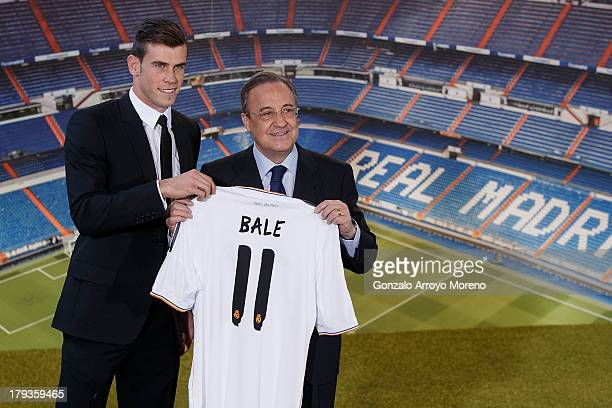 Gareth Bale shows his new Real Madrid shirt as he stands alongside president Florentino Perez during his presentation as a new Real Madrid player at...