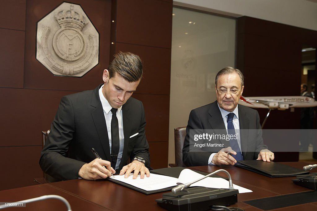 Gareth Bale (L) signs his contract with Real Madrid's President Florentino Perez during his official presentation as a new Real Madrid player at Estadio Santiago Bernabeu on September 2, 2013 in Madrid, Spain.