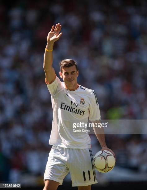 Gareth Bale waves to fans in his new Real Madrid shirt during his official unveiling at estadio Santiago Bernabeu on September 2 2013 in Madrid Spain