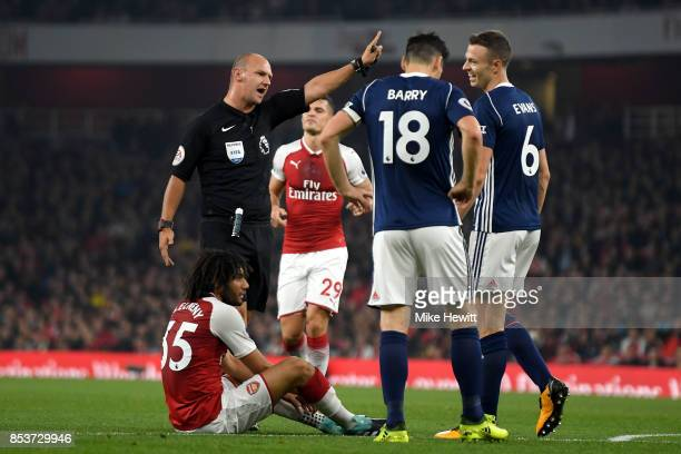 Gareth Barry and Jonny Evans of West Bromwich Albion react as referee Robert Madley awards a free kick during the Premier League match between...
