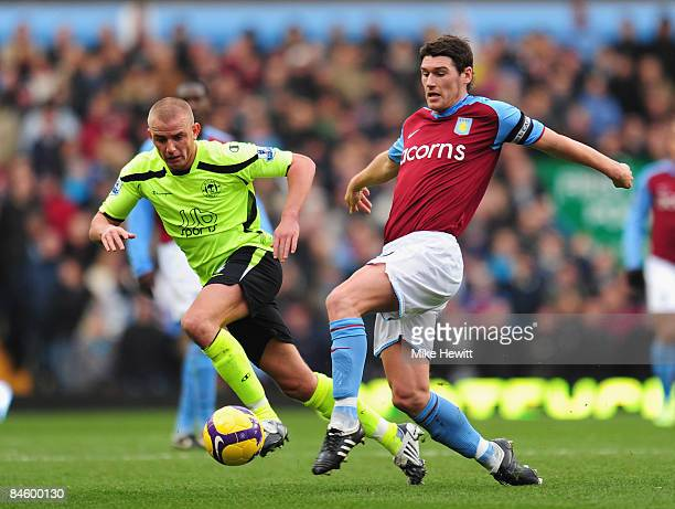 Gareth Barry of Aston Villa is challenged by Lee Cattermole of Wigan during the Barclays Premier League match between Aston Villa and Wigan Athletic...
