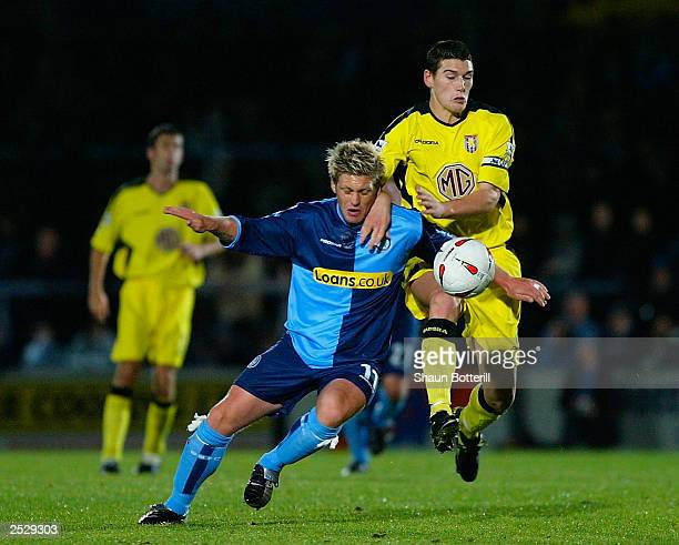 Gareth Barry of Aston Villa tackles Dannie Bulman of Wycombe Wanderers during the Carling Cup Second Round match between Wycombe Wanderers and Aston...