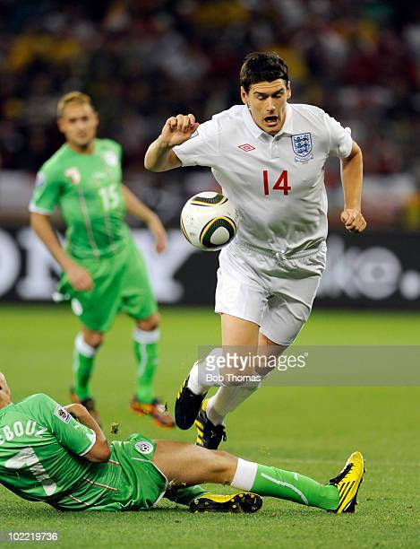 Gareth Barry of England jumps over the tackle of Ryad Boudebouz of Algeria during the 2010 FIFA World Cup South Africa Group C match between England...