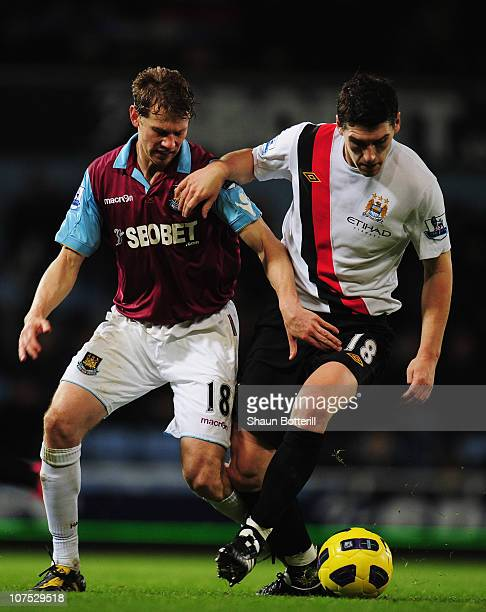 Gareth Barry of Manchester City holds off the challenge of Jonathan Spector of West Ham United during the Barclays Premier League match between West...