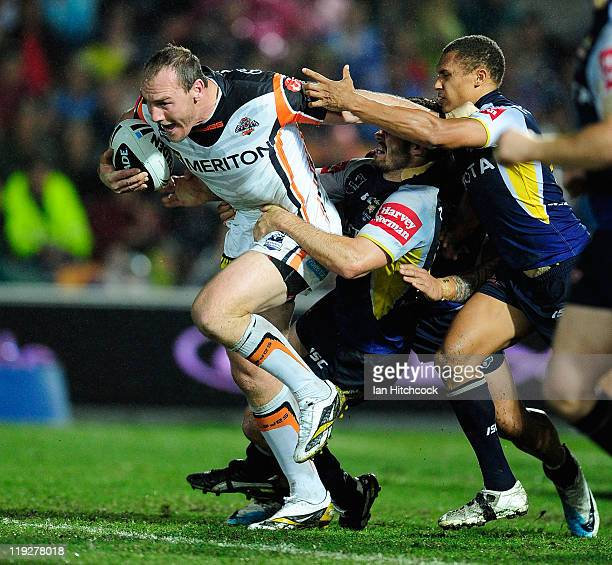 Gareth Ellis of the Tigers loos to get through the Cowboys defence of Ray Thompson and Dallas Johnson during the round 19 NRL match between the North...