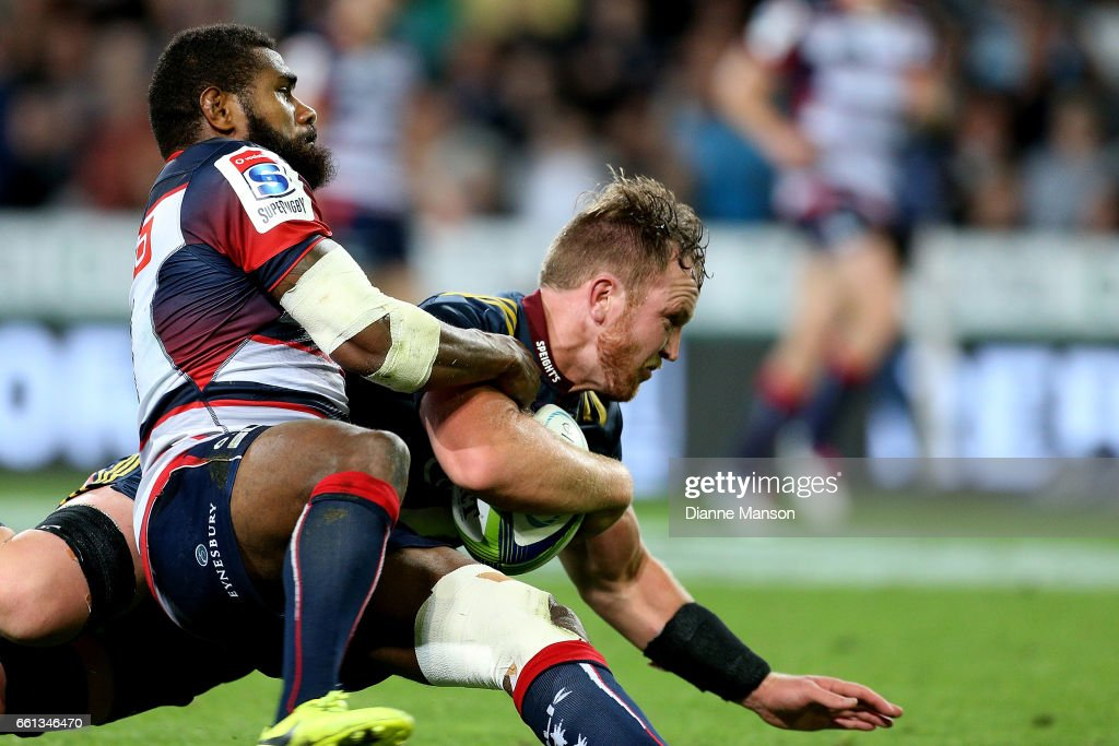 Gareth Evans (R) of the Highlanders dives over to score a try while in the tackle of Marika Koroibete of the Rebels during the round six Super Rugby match between the Highlanders and the Rebels at Forsyth Barr Stadium on March 31, 2017 in Dunedin, New Zealand.