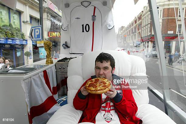 Gareth Howard takes a bite from his first Goodfella's Pizza as he starts his campaign to spend the entire World Cup in a perspex box on the back of a...