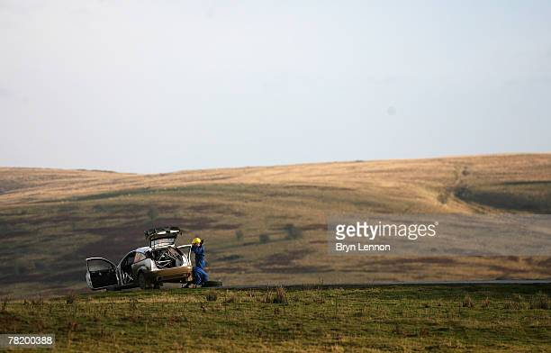 Gareth Jones of Great Britain and Codriver David Moynihan of Ireland repair a puncture on their Ford Focus after the Crychan stage of the 2007 FIA...