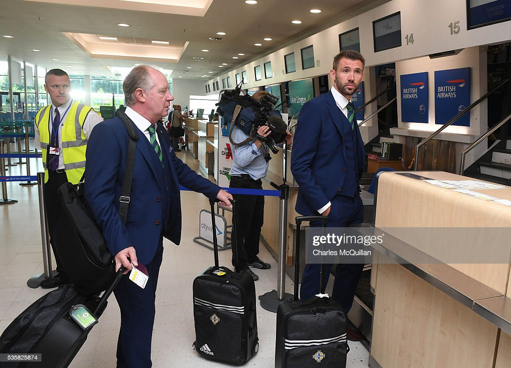 Gareth McAuley (R) makes his way to the check-in desk alongside Jimmy Nicholl (L) before Northern Ireland's training camp departure at George Best City Airport on May 30, 2016 in Belfast, Northern Ireland. Northern Ireland have qualified for the Euro 2016 football championship finals in France, the first time the province has qualified for an international football tournament final since 1986.