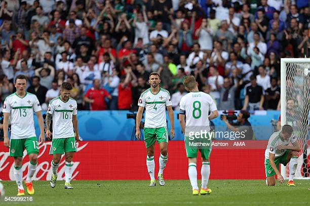 Gareth McAuley of Northern Ireland and his teammates react after he scored an own goal to make the score 10 during the UEFA Euro 2016 Round of 16...