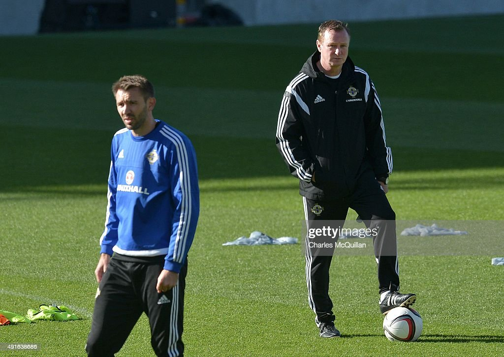 Gareth McAuley of Northern Ireland is watched by manager Michael O'Neill (R) as the international football squad train at Windsor Park on October 7, 2015 in Belfast, Northern Ireland. Northern Ireland host Greece in a Euro 2016 Group F game at Windsor Park on Thursday evening.