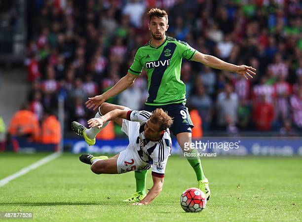 Gareth McAuley of West Bromwich Albion is challenged by Jay Rodriguez of Southampton during the Barclays Premier League match between West Bromwich...
