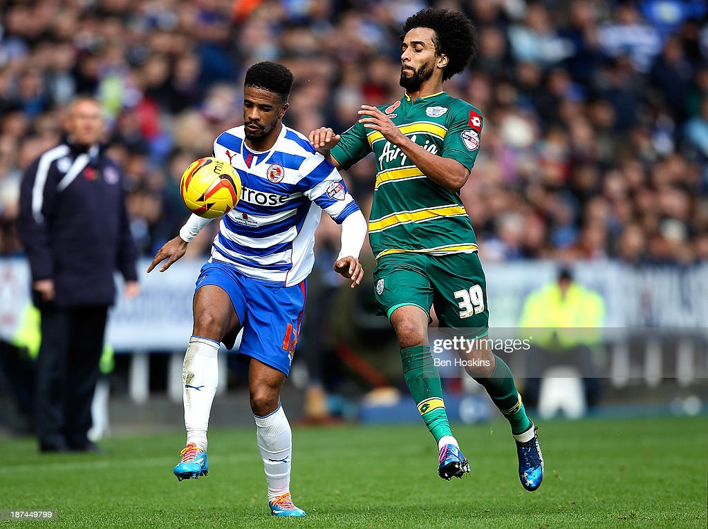 Gareth McCleary of Reading holds off pressure from <a gi-track='captionPersonalityLinkClicked' href=/galleries/search?phrase=Benoit+Assou-Ekotto&family=editorial&specificpeople=709848 ng-click='$event.stopPropagation()'>Benoit Assou-Ekotto</a> of QPR during the Sky Bet Championship match between Reading and Queens Park Rangers at Madejski Stadium on November 09, 2013 in Reading, England,