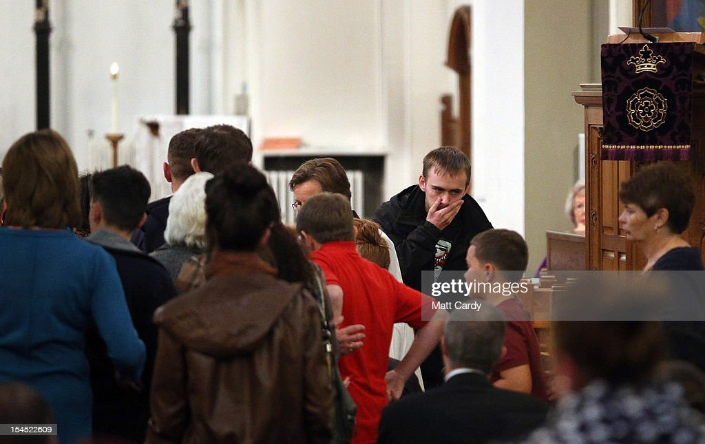 Gareth Menzies, whose sister Karina Menzies was killed on Friday, covers his mouth after he lights a candle as people gather for a special service of prayer and reflection held for those affected by the hit-and-run incidents in Cardiff at the Church of the Resurrection on Grand Avenue on October 21, 2012 in Cardiff, Wales. Detectives are questioning a 31-year-old man arrested on suspicion of murder after a series of hit-and-runs in Cardiff that left a woman dead and 13 people injured. Nine casualties, five of them children, are still in hospital. Two adults are in critical but stable conditions.