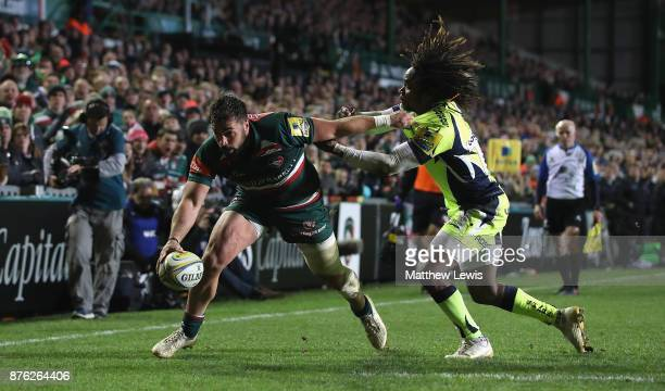Gareth Owen of Leicester Tigers holds off Marland Yarde of Sale Sharks to score a try during the Aviva Premiership match between Leicester Tigers and...