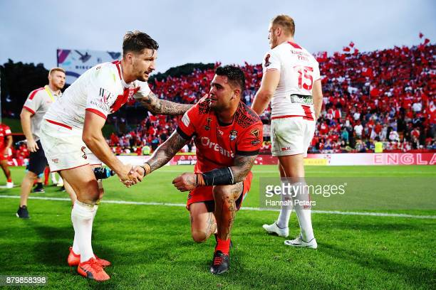 Gareth Widdop of England helps Andrew Fifita of Tonga of Tonga his feet during the 2017 Rugby League World Cup Semi Final match between Tonga and...