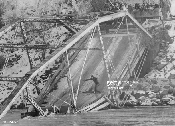 Garfield County road crewmen fish a backhoe from the Colorado River after a pickup truck' pulling the machine collapsed a steel bridge about TO miles...