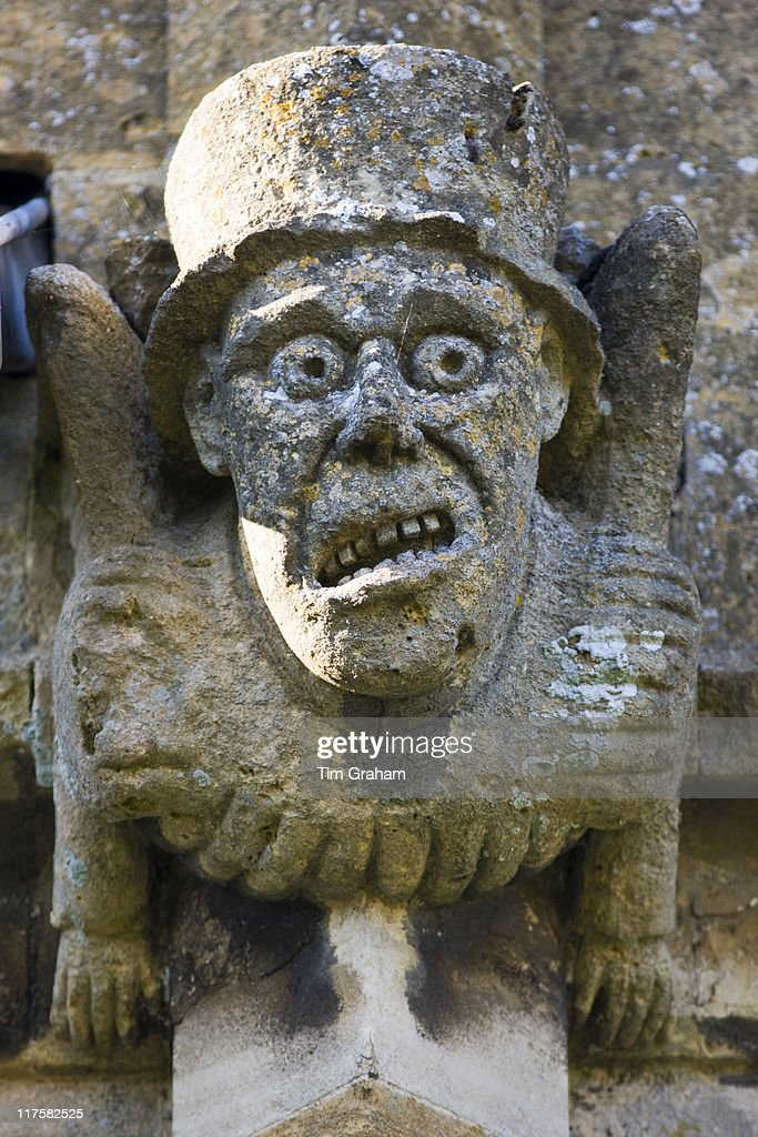 Gargoyle carved stone grotesque carving of a figure on st