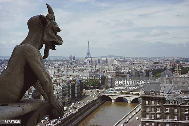 A gargoyle on the top of Notre Dame de Paris in Paris France with the Eiffel Tower in the distance circa 1960