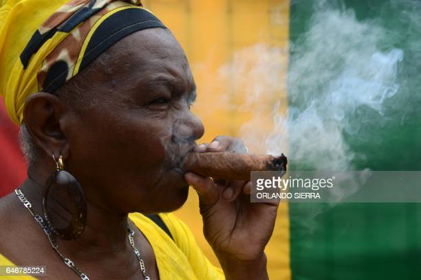 A Garifuna woman smokes a cheroot during a protest in Tegucigalpa on March 1 2017 / AFP PHOTO / ORLANDO SIERRA