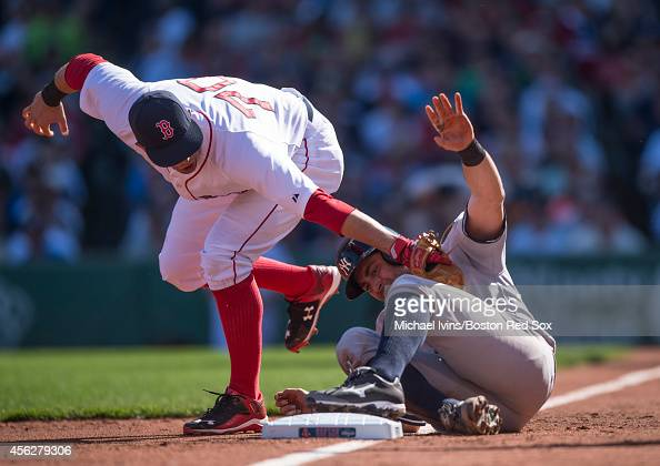 Garin Cecchini of the Boston Red Sox attempts to tag Francisco Cervelli of the New York Yankees after he advanced on a wild pitch by Clay Buchholz...
