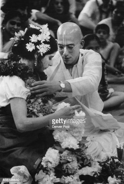 Garlands are exchanged by the couple near end of ceremony He is wearing a yellow dhoti yellow signifying he's married Credit Denver Post Inc