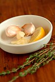 Garlic and lemon in a white bowl on table.