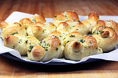 A tray of freshly baked garlic knots on parchment paper