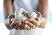 Woman holding garlic in her hands.
