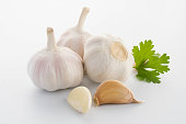 garlic with leaves of parsley isolated on white