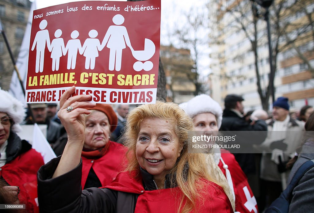 Garlonn, the spokeswoman of the Polish 'Knights of Christ the King' ('Chevaliers du Christ-Roi de l'Univers' in French) holds a placard reading 'Family is sacred' during a protest organized by French Christian fundamentalist Civitas Institute against same-sex marriage on January 13, 2013 in Paris. Tens of thousands march in Paris on January 13 to denounce government plans to legalise same-sex marriage and adoption which have angered many Catholics and Muslims, France's two main faiths, as well as the right-wing opposition. The French parliament is to debate the bill -- one of the key electoral pledges of Socialist President -- at the end of this month. AFP PHOTO / KENZO TRIBOUILLARD