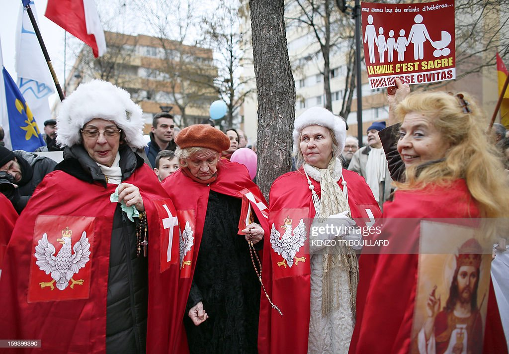 Garlonn (R), the spokeswoman of the Polish 'Knights of Christ the King' ('Chevaliers du Christ-Roi de l'Univers' in French) holds a placard reading 'Family is sacred' beside other women of her religious movement during a protest organized by French Christian fundamentalist Civitas Institute against same-sex marriage on January 13, 2013 in Paris. Tens of thousands march in Paris on January 13 to denounce government plans to legalise same-sex marriage and adoption which have angered many Catholics and Muslims, France's two main faiths, as well as the right-wing opposition. The French parliament is to debate the bill -- one of the key electoral pledges of Socialist President -- at the end of this month.