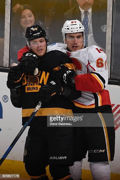 Garnet Hathaway of the Calgary Flames holds back David Pastrnak of the Boston Bruins at the TD Garden on November 25 2016 in Boston Massachusetts