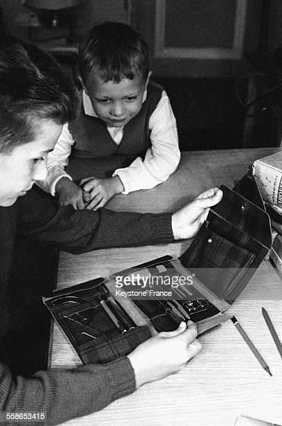 Garçon avec son frère regardant sa nouvelle trousse avant la rentrée scolaire à Paris France en 1963