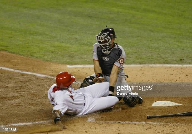 Garret Anderson of the Anaheim Angels is tagged out at home by Benito Santiago of San Francisco Giants in the third inning of game seven during the...