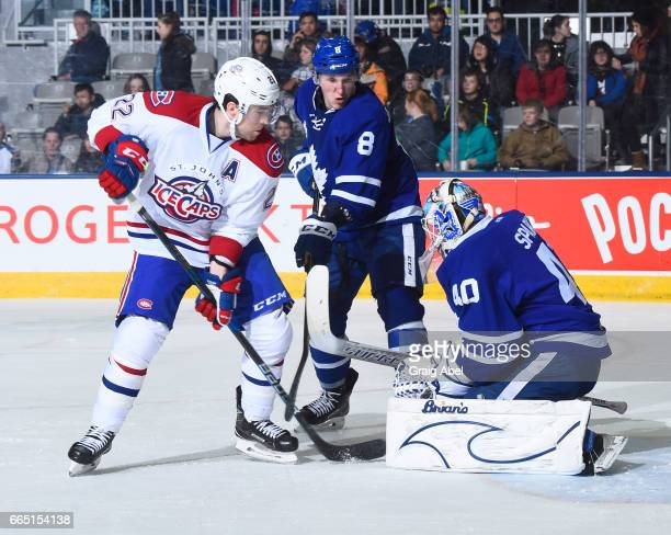 Garret Sparks of the Toronto Marlies stops a shot while Chris Terry of the St John's IceCaps and Travis Dermott of the Marlies battle in front during...