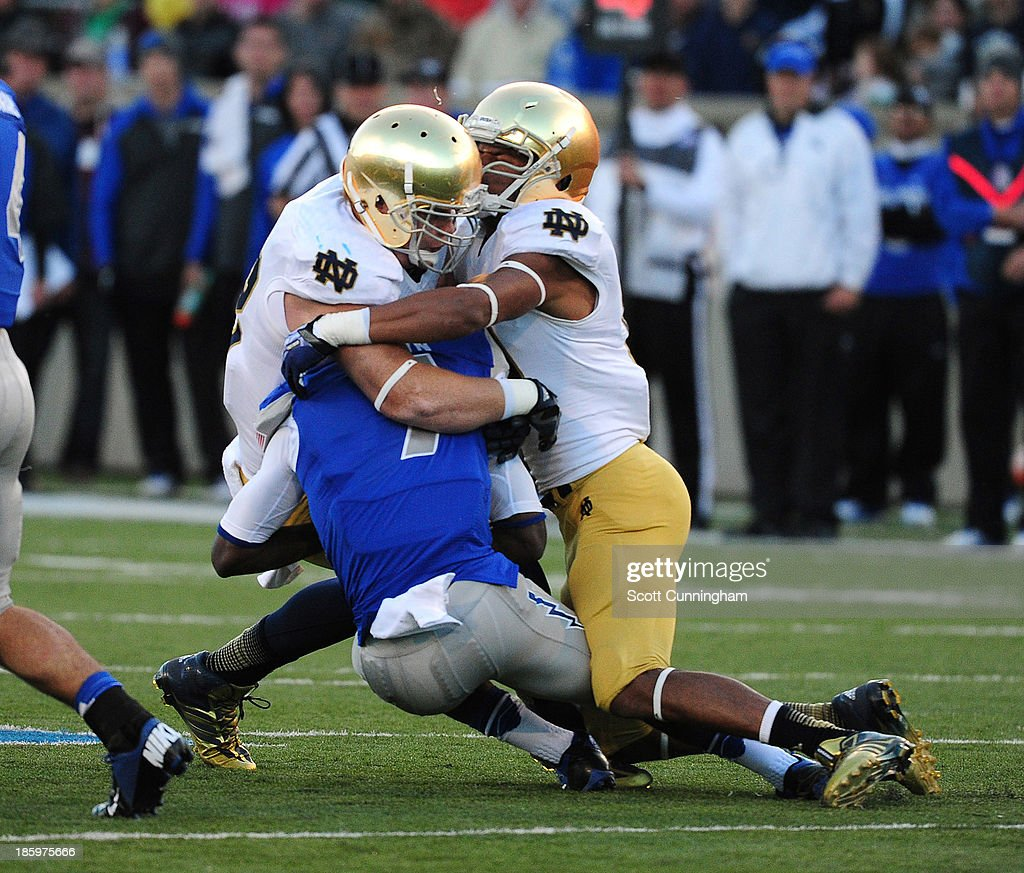 Garrett Brown #7 of the Air Force Falcons is tackled by Dan Fox #48 and Jaylon Smith #9 of the Notre Dame Fighting Irish at Falcon Stadium on October 26, 2013 in Colorado Springs, Colorado.