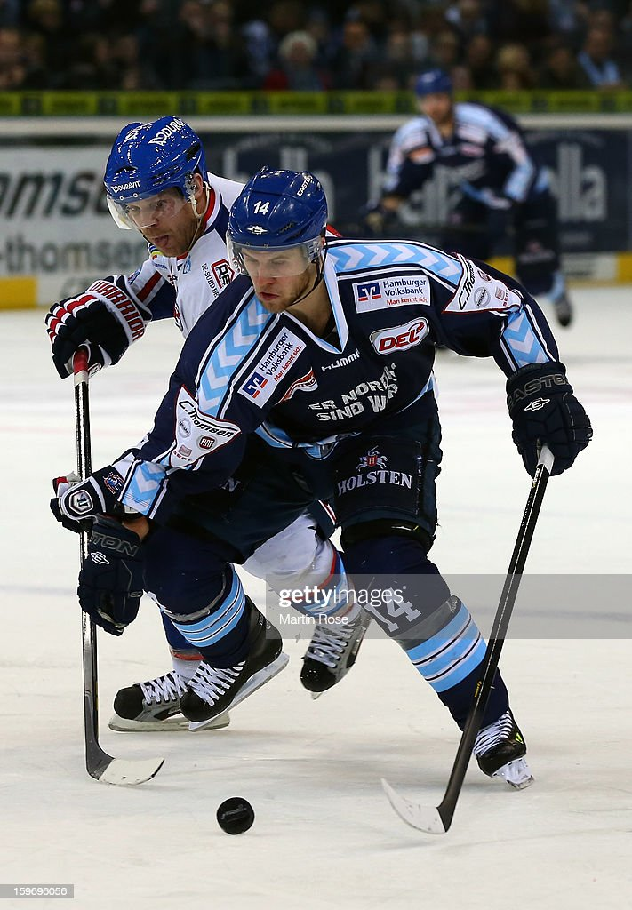 Garrett Festerling (#14) of Hamburg battles for the puck with Chris MacDonald (back) of Mannheim during the DEL match between Hamburg Freezers and Adler Mannheim at O2 World on January 18, 2013 in Hamburg, Germany.