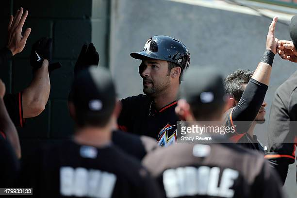 Garrett Jones of the Miami Marlins is congratulated by teammates following a first inning home run against the Houston Astros at Osceola County...