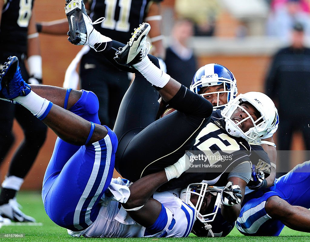 Garrett Patterson #24 and David Rees #80 of the Duke Blue Devils tackle Tyree Harris #12 of the Wake Forest Demon Deacons during play at BB&T Field on November 23, 2013 in Winston Salem, North Carolina. Duke won 28-21.
