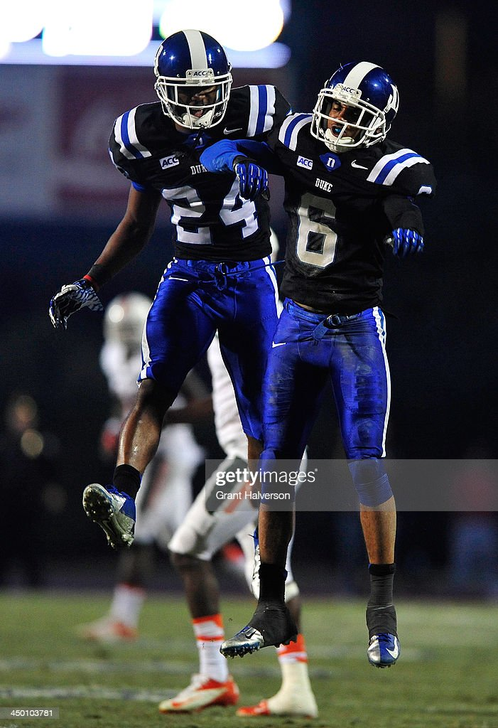 Garrett Patterson #24 and Ross Cockrell #6 of the Duke Blue Devils celebrate after making a defensive stop on fourth down late in the fourth quarter of a winover the Miami Hurricanes at Wallace Wade Stadium on November 16, 2013 in Durham, North Carolina. Duke won 48-30.