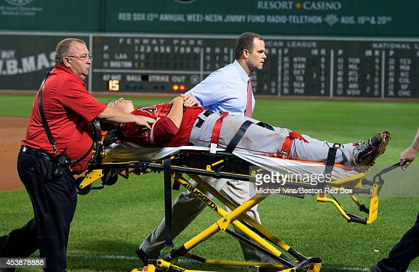 Garrett Richards of the Los Angeles Angels of Anaheim is wheeled off the field after sustaining an injury while attempting to cover first base...