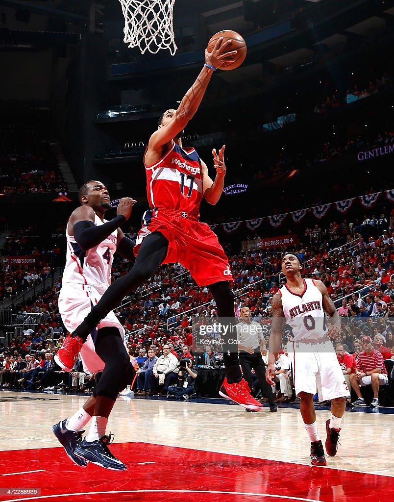 Garrett Temple of the Washington Wizards drives against Paul Millsap and Jeff Teague of the Atlanta Hawks during Game Two of the Eastern Conference...