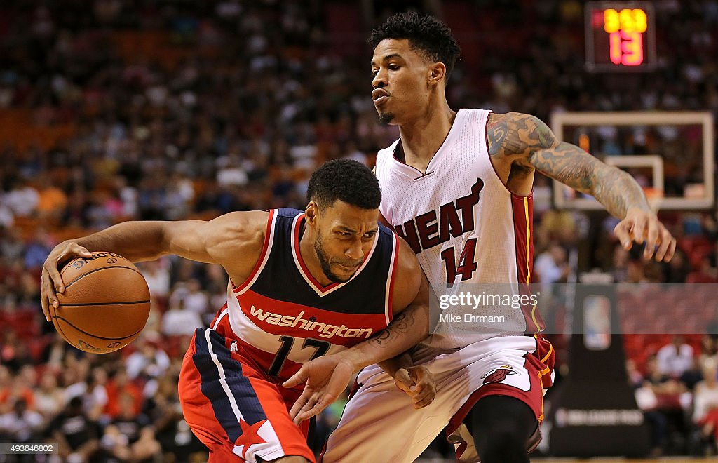 Garrett Temple of the Washington Wizards drives on Gerald Green of the Miami Heat during a preseason game at American Airlines Arena on October 21...